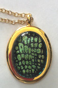 Click for a larger photo of the Clear Glass on Greenish Gold Reptile Patterned Oval in Gold-plated Setting